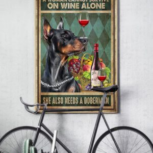 A woman cannot survive on wine alone she also needs a doberman poster